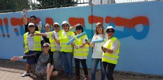 בנצי עם נאמנות השכונה על רקע ציור הקיר שציירו