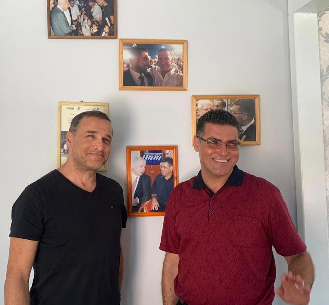 נאיל זועבי עם ליאור אקרמן על רקע קיר ראשי הממשלות והנשיאים שביקרו בביתו של נאיל